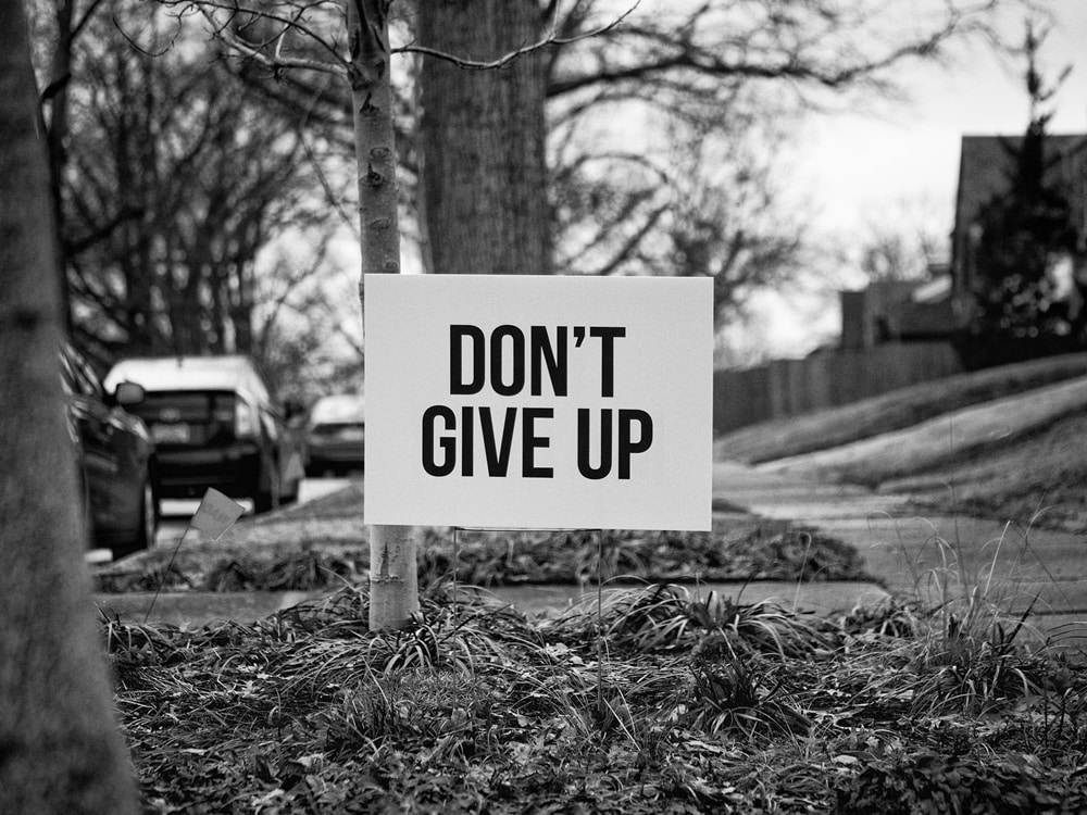 Don't give up sign sidewalk Sara Blakely quotes black and white grass cars trees